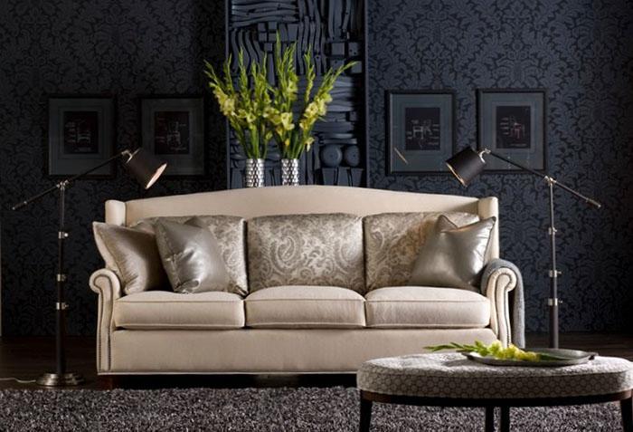Бежевый диван на фоне черных обоев