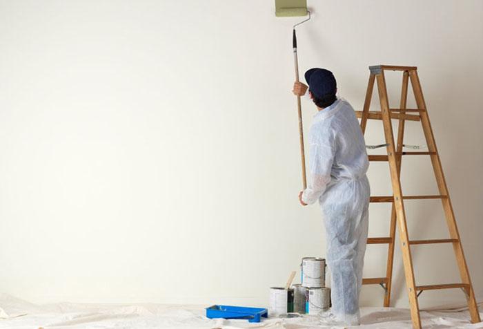 Мужчина красит стену