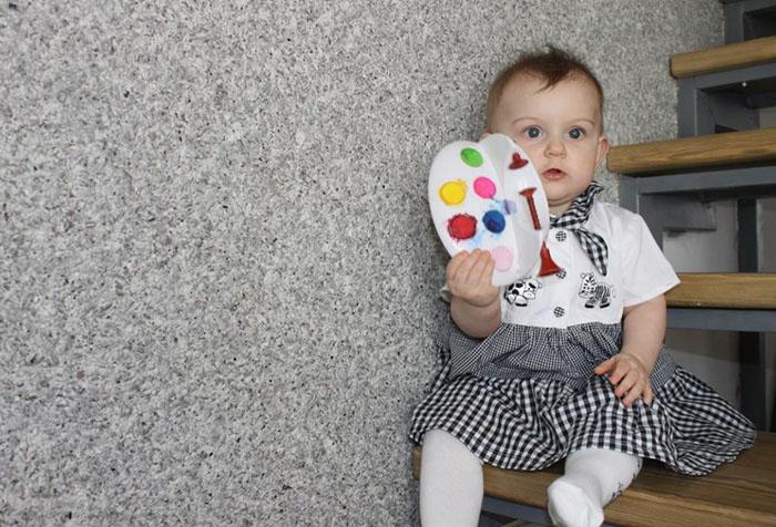 Ребенок у стены с жидкими обоями