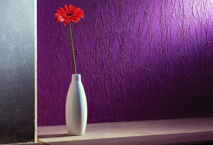 Цветок в вазе на фоне фиолетовых обоев