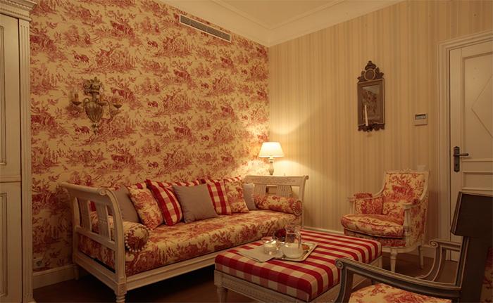 Сочетание пастельных цветов и разных узоров в комбинации обоев в гостиной